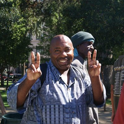 an image of an African-American man in a blue shirt holding up double peace signs with his hands