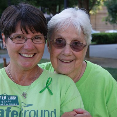 an image of two older women in green shirts standing together and smiling at an outdoor event