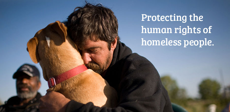 an image of a man sitting outdoors holding his dog closely in a loving embrace